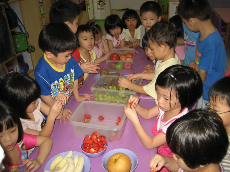 Children preparing fruits for healthy eating lesson
