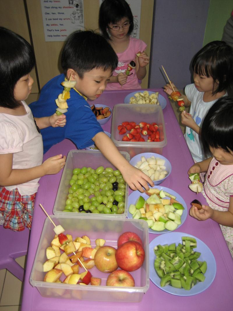 Children making fruit kebab